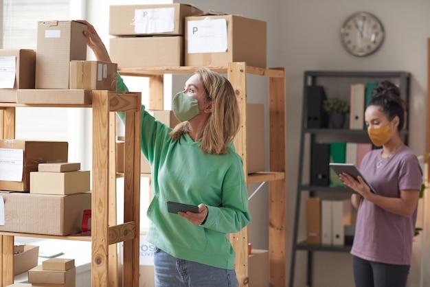 Due giovani donne in maschere protettive utilizzando computer tablet mentre si lavora con i pacchi di cartone in officina