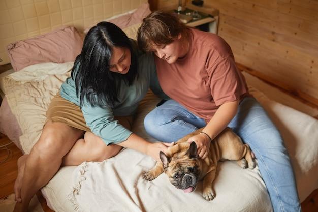 Due giovani donne sedute sul letto in camera da letto e accarezzando il loro cane si prendono cura del loro animale domestico