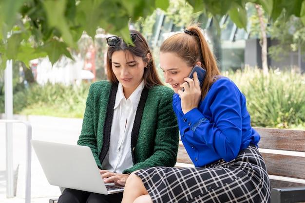 Due giovani donne sedute su una panchina di strada che lavorano sul loro laptop che punta allo schermo
