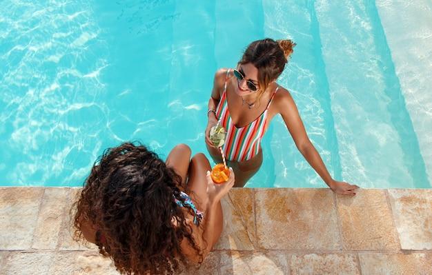 Due giovani donne in costume da bagno rilassarsi e bere cocktail tropicali nella vista dall'alto della piscina si chiuda