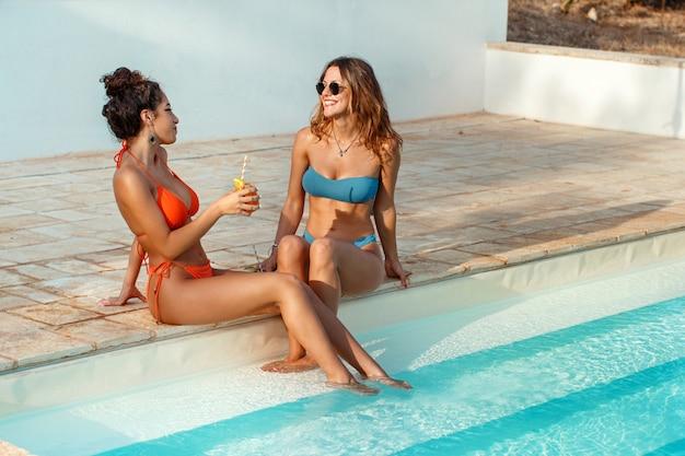 Due giovani donne in costume da bagno rilassarsi e bere cocktail tropicali in piscina