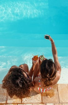 Due giovani donne in costume da bagno che prendono selfie con un telefono e bevono cocktail tropicali nella vista dall'alto della piscina