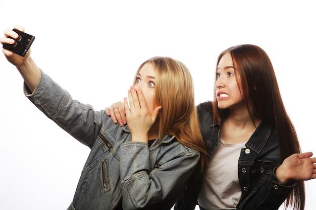 Due giovani donne che prendono selfie con il telefono cellulare, isolate su bianco