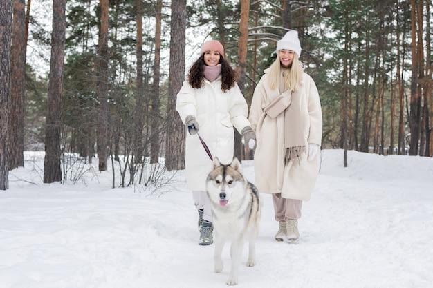 Due giovani donne che camminano cane