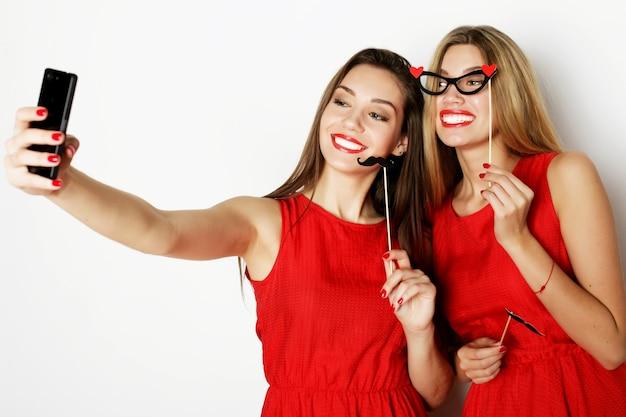 Due giovani donne che indossano abito rosso tenendo selfie con il telefono cellulare