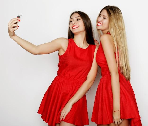 Due giovani donne che indossano un abito rosso che si fanno selfie con il cellulare