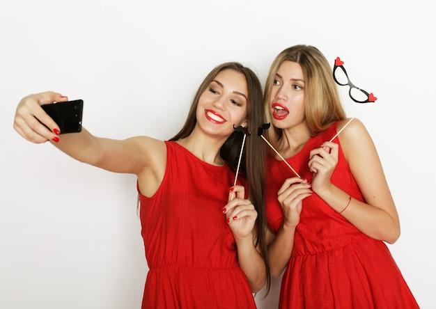 Due giovani donne che indossano abito rosso tenendo selfie