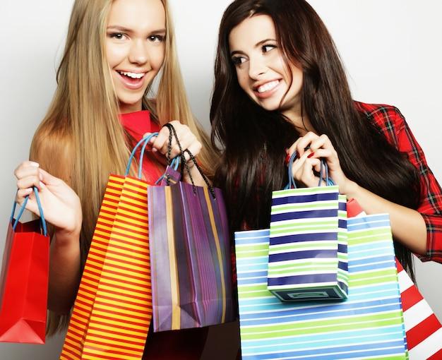 Due giovani donne che indossano un vestito rosso con le borse della spesa
