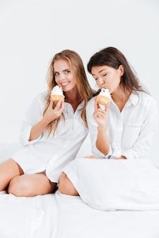Due giovani donne in camicie bianche che tengono in mano dei cupcake mentre sono sedute sul letto