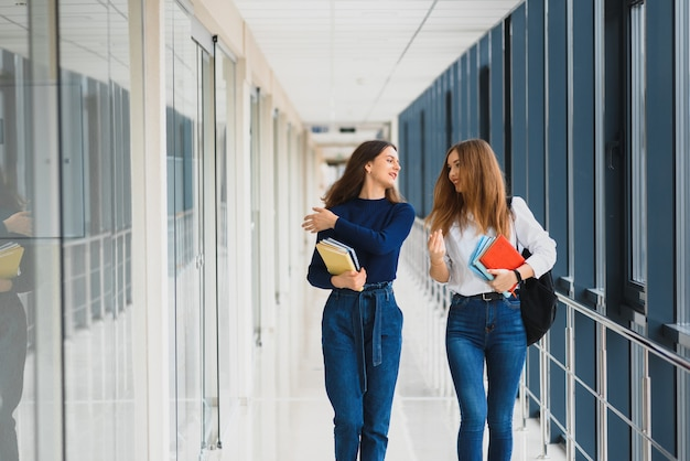 Due giovani donne con il libro in chat mentre si trovava nel corridoio del college