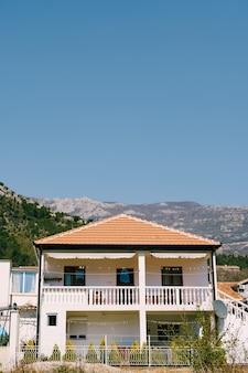 Una casa a due piani con balconi e piastrelle marroni in montagna contro il cielo blu