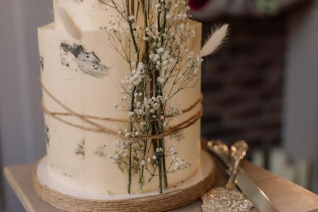 Torta a due livelli decorata con fiori secchi in stile boho