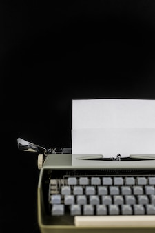 Macchina da scrivere sul tavolo su un muro nero con carta bianca con spazio vuoto. luogo di lavoro dello scrittore o dell'autore. idea concept.