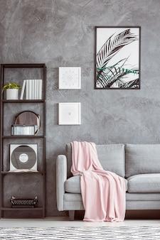 Macchina da scrivere e vinile sullo scaffale accanto al divano grigio con copriletto rosa contro il muro di cemento con poster