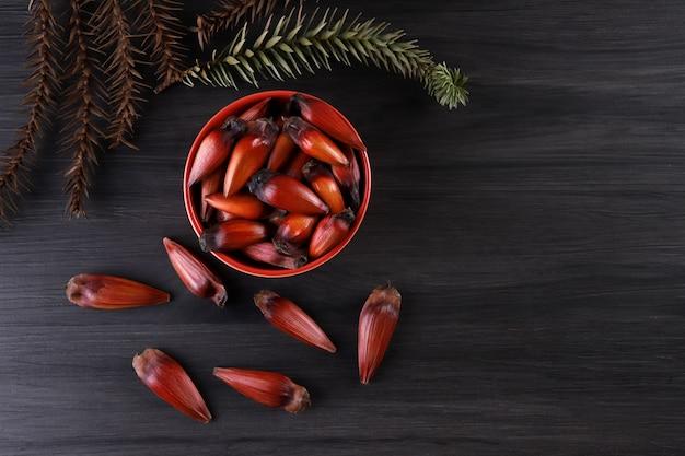 Semi di araucaria tipici usati come condimento nella cucina brasiliana in inverno. dadi brasiliani del pignone in ciotola di legno marrone e rossa su fondo di legno grigio.