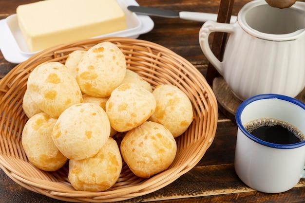Panino tipico del formaggio brasiliano su un cestino con burro e caffè