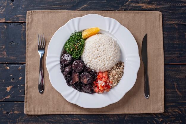 Piatto tipico brasiliano chiamato feijoada. a base di fagioli neri, maiale e salsiccia. vista dall'alto