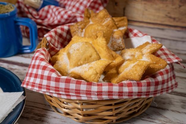 Tipico fritto di patate dolci e mele cotogne su vassoio accompagnato dal classico mate su un vecchio tavolo di legno. concetto di cucina etnica o regionale. avvicinamento.