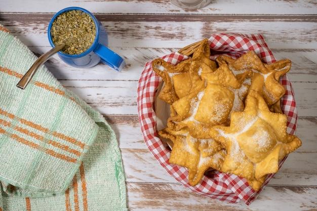Tipico fritto di patate dolci e mele cotogne su vassoio accompagnato dal classico mate su un vecchio tavolo di legno. concetto di cucina etnica o regionale. vista dall'alto