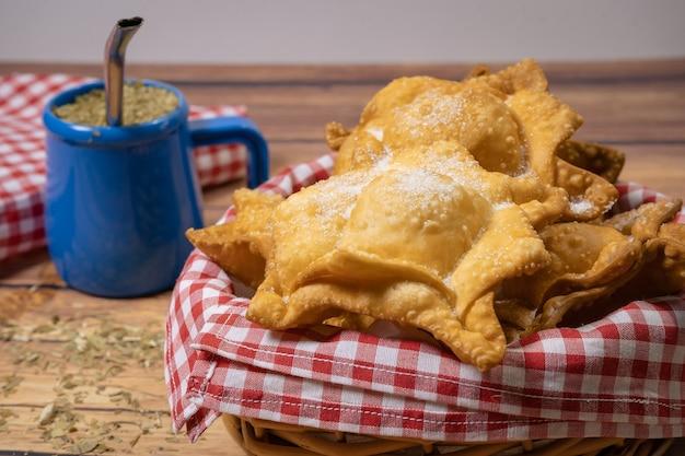 Tipico fritto di patate dolci e mele cotogne su vassoio accompagnato dal classico mate su un rustico tavolo di legno. concetto di cucina etnica o regionale. alta vista.