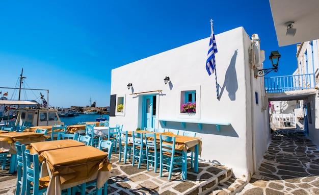 Tipica taverna greca con tavoli e sedie colorate nel porto di naoussa
