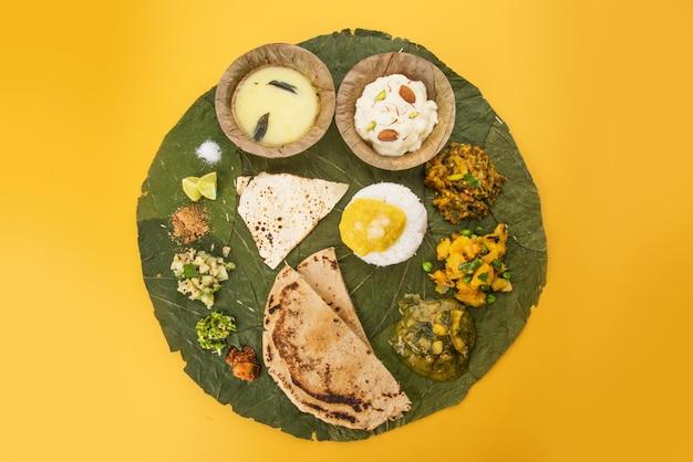 Tipico piatto di cibo maharashtrian sano o thali pieno di sostanze nutritive servito su piatto costituito da foglie verdi degradabili, messa a fuoco selettiva