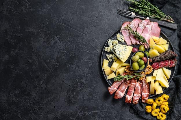 Antipasto tipico italiano con prosciutto, prosciutto, formaggio e olive. vista dall'alto. sfondo di copyspace