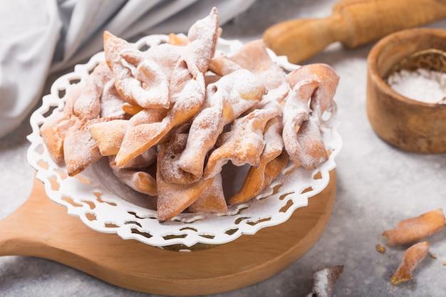 Tipiche frittelle di carnevale italiane spolverate con zucchero a velo sul tavolo di cemento.