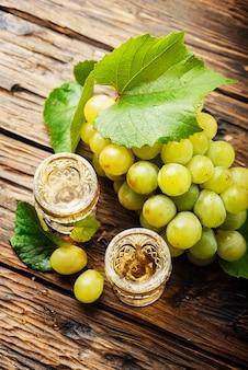 Tipica grappa italiana d'oro con uva gialla sul tavolo di legno