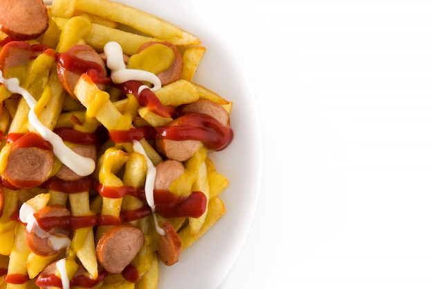 Salchipapa tipico dell'america latina. salsicce con patatine fritte, ketchup, senape e maionese isolati su sfondo bianco vista dall'alto copia spazio