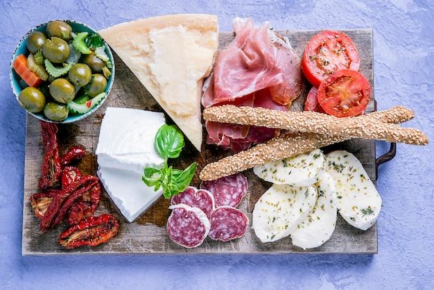 Antipasto italiano tipico mediterraneo a base di salumi, salsicce, olive e mozzarella