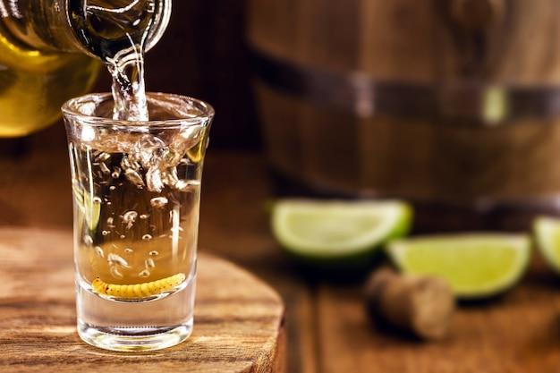 Tipica bevanda messicana bottiglia che riempie un bicchiere di mezcal (o mescal), una rara bevanda distillata messicana che contiene una larva afrodisiaca o un verme all'interno