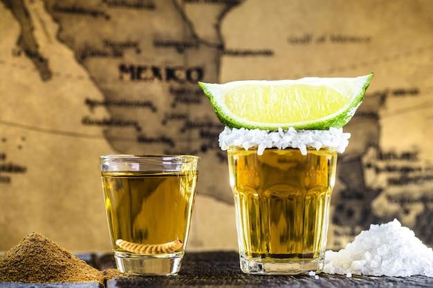 Tipiche bevande messicane, mezcal con sale, pepe e larva accanto alla tequila con limone e sale, con mappa del messico in superficie