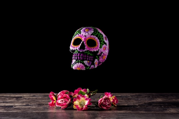 Tipico diadema messicano con teschio e fiori su sfondo nero. dia de los muertos.