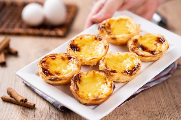 Tipiche torte di crema pasticcera portoghesi. pasticceria tradizionale portoghese. tenendo da uno chef.