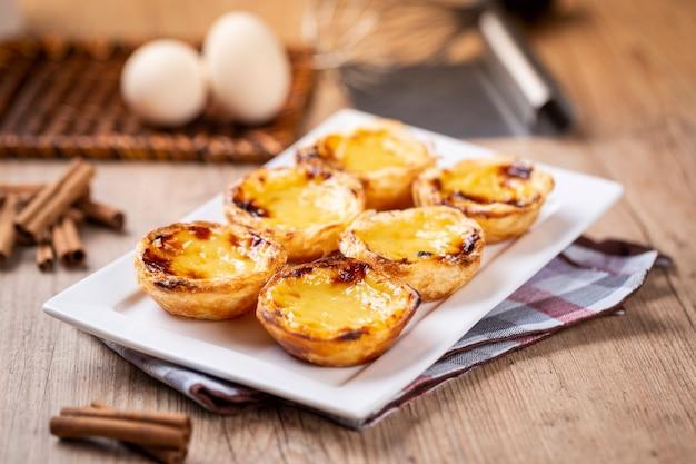 Tipiche torte di crema pasticcera portoghesi. pasticceria tradizionale portoghese. su un tavolo di legno.