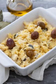 Piatto tipico portoghese uova con baccalà e olive nel piatto bianco bacalhau a lisbonense