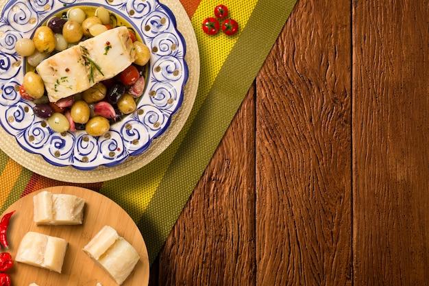 Un piatto tipico portoghese con baccalà chiamato bacalhau do porto in un piatto portoghese originale visto dall'alto.