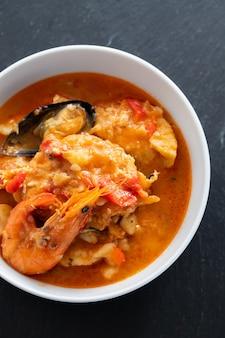 Pesce portoghese tipico e stufato di frutti di mare caldeirada nel piatto sulla superficie in ceramica
