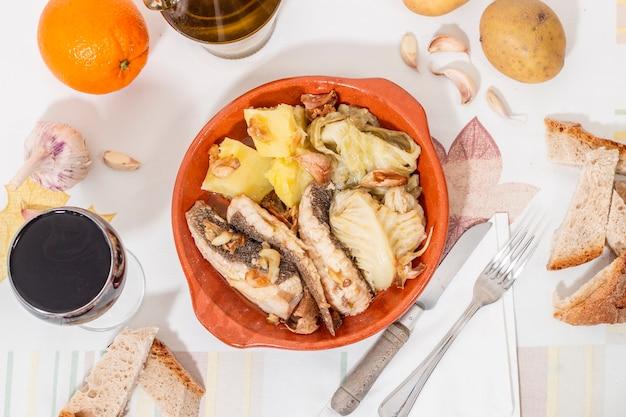 Tipico pesce di razza portoghese fatto in casa con patate, aglio e olio d'oliva. Foto Premium