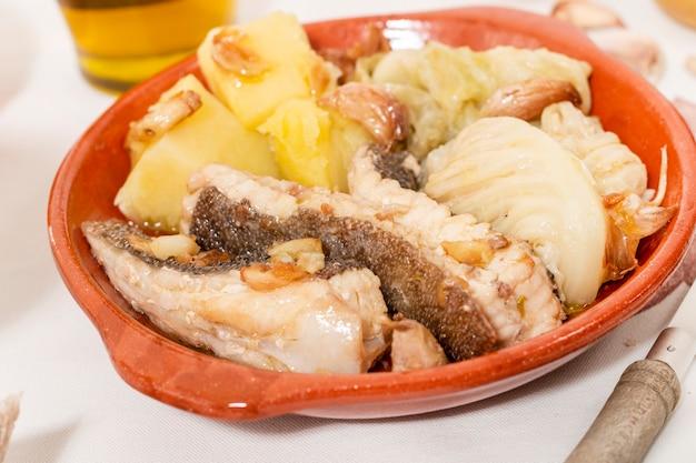 Tipico pesce di razza portoghese fatto in casa con patate, aglio e olio d'oliva.