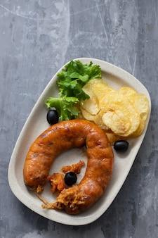 Salsiccia affumicata portoghese tipica alheira con patatine fritte e insalata fresca