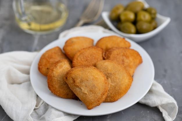 Tipico spuntino portoghese con carne rissois de carne su fondo in ceramica