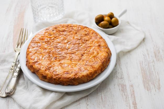 Tortilla tipica spagnola dell'alimento sul piatto bianco su fondo di legno bianco