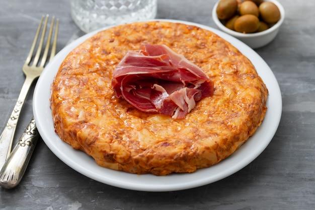 Cibo tipico spagnolo tortilla con carne affumicata e patate sul piatto bianco