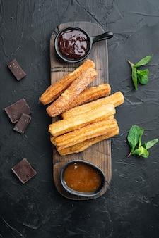Tipico spagnolo churros snack, pasta fritta servita solitamente con salsa calda al caramello al cioccolato impostato, su sfondo nero, vista dall'alto laici piatta