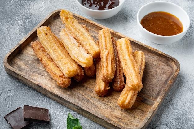 Churros snack tipici spagnoli, pasta fritta servita solitamente con salsa piccante al cioccolato e caramello, su sfondo grigio