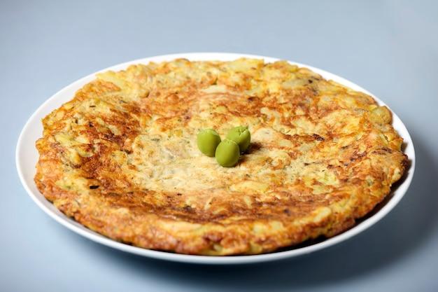 Una tipica tortilla spagnola decorata con olive su sfondo chiaro