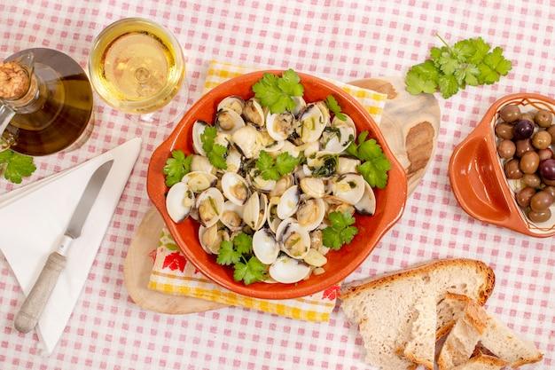Pasto portoghese tipico dell'antipasto di vongole con aglio, olio d'oliva e prezzemolo.