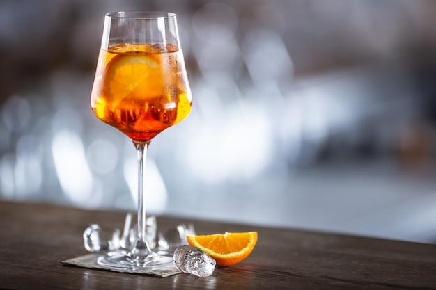 Tipico drink estivo aperol spritz servito in un bicchiere di vino con aperol, prosecco, soda e una fetta di arancia.